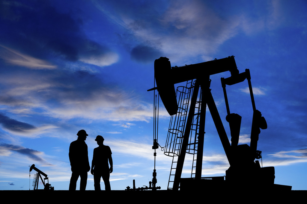 A royalty free image from the oil and gas industry of two oil workers in an oil field at duck.